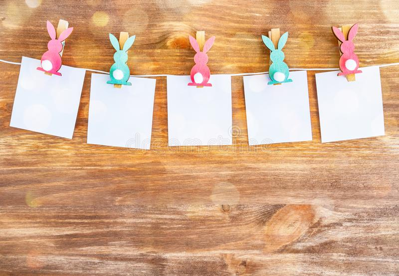 White blanks with rabbits pins on wooden background. Easter decoration.  royalty free stock photo
