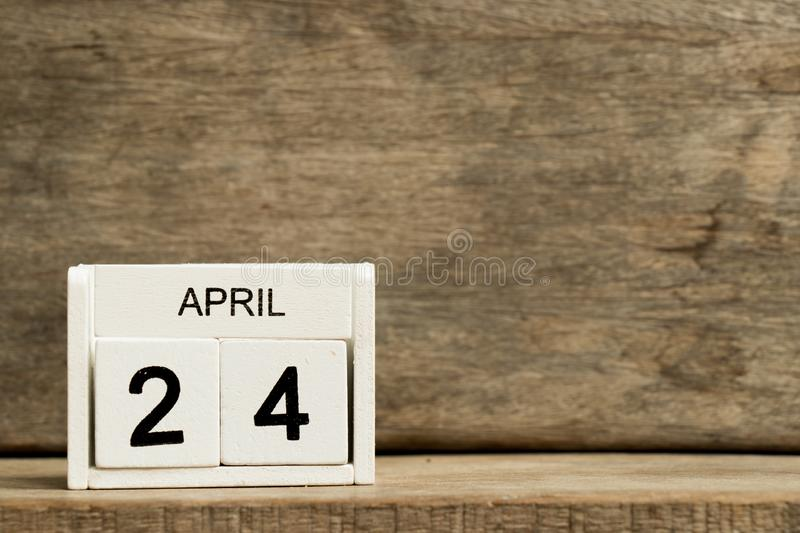 .White block calendar present date 24 and month April on wood background. Design, element, year, business, graphic, week, template, day, office, time, holiday royalty free stock photography
