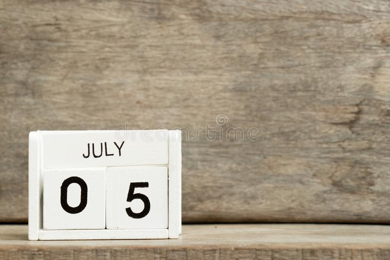 White block calendar date 5 and month July on wood background stock images