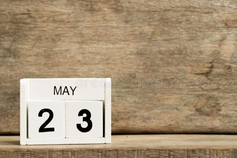 White block calendar present date 23 and month May. On wood background stock photo