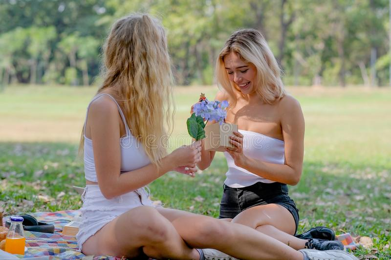 White blond girl get gift from her friend with surprise and happy action in the garden with day light stock images