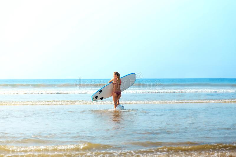 White blonde surfer girl with surfboard goes to sea stock photo