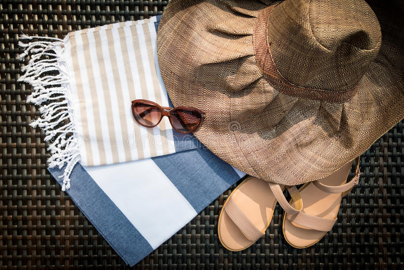 A white, blue and beige Turkish towel, sunglasses, beige leather ladies sandals and straw hat on a rattan lounger. royalty free stock photo