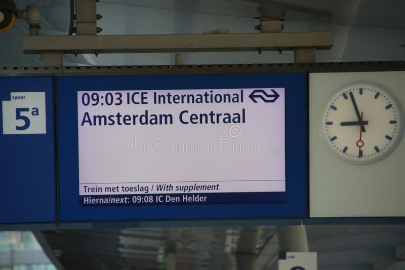 White and blue departure information display at platform with information for the international ICE train from Berlin to Amsterdam royalty free stock images