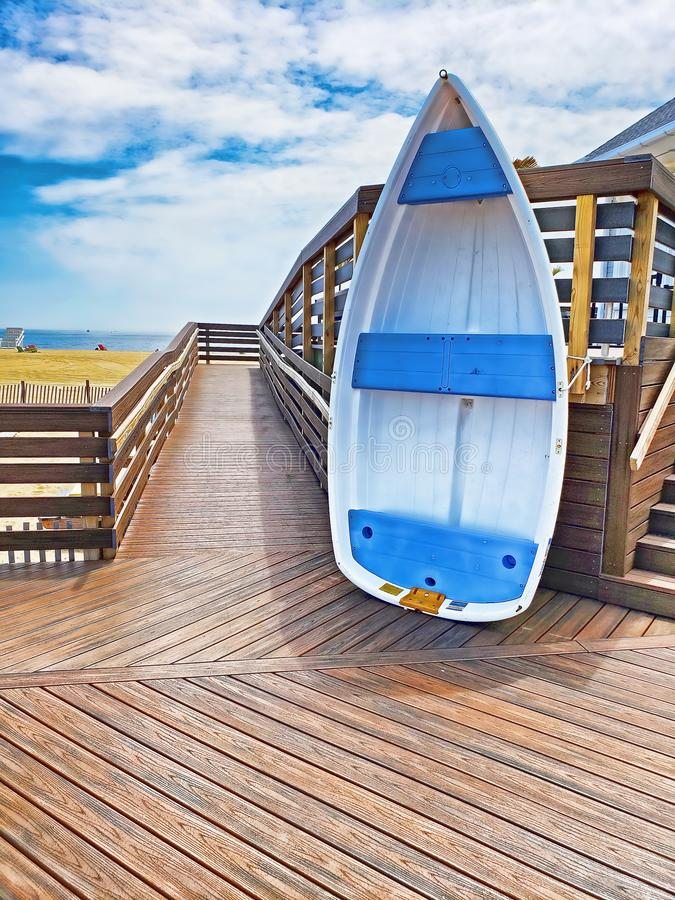 White and blue dingy stood up on its stern on a boardwalk. The walkway slopes up and to a deck on the right. In the background is the beach, a sliver of sea, and royalty free stock images
