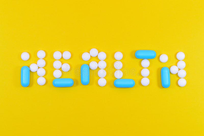 White and Blue Health Pill and Tablet Letter Cutout on Yellow Surface stock photos
