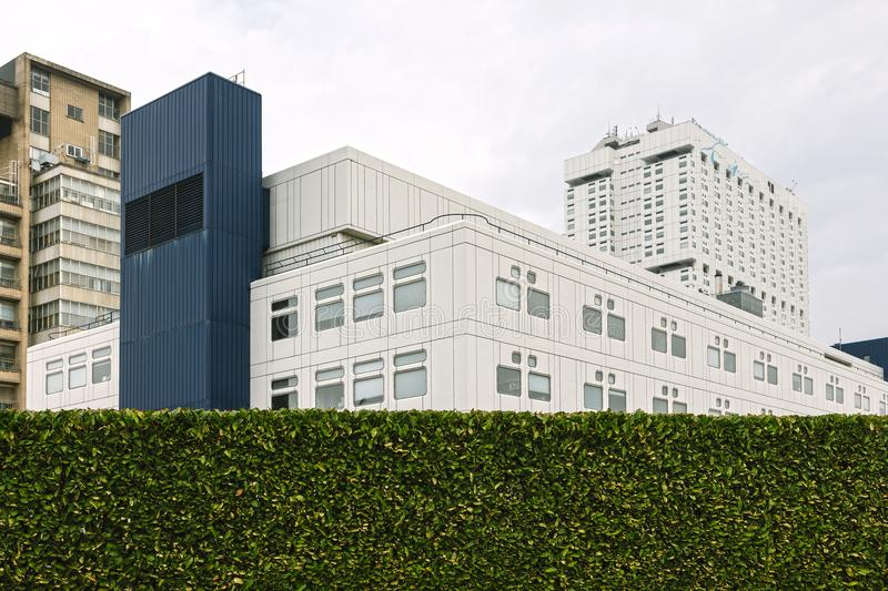 White and Blue High-rise Building Behind Bush Wall stock image