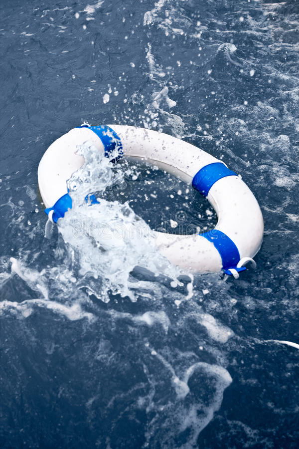 White and blue lifebelt, lifebuoy in ocean storm wave. White and blue lifebelt, lifebuoy in a rescue on ocean storm wave stock photography