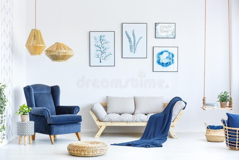 White and blue living room. With sofa, armchair, lamp, posters royalty free stock photos