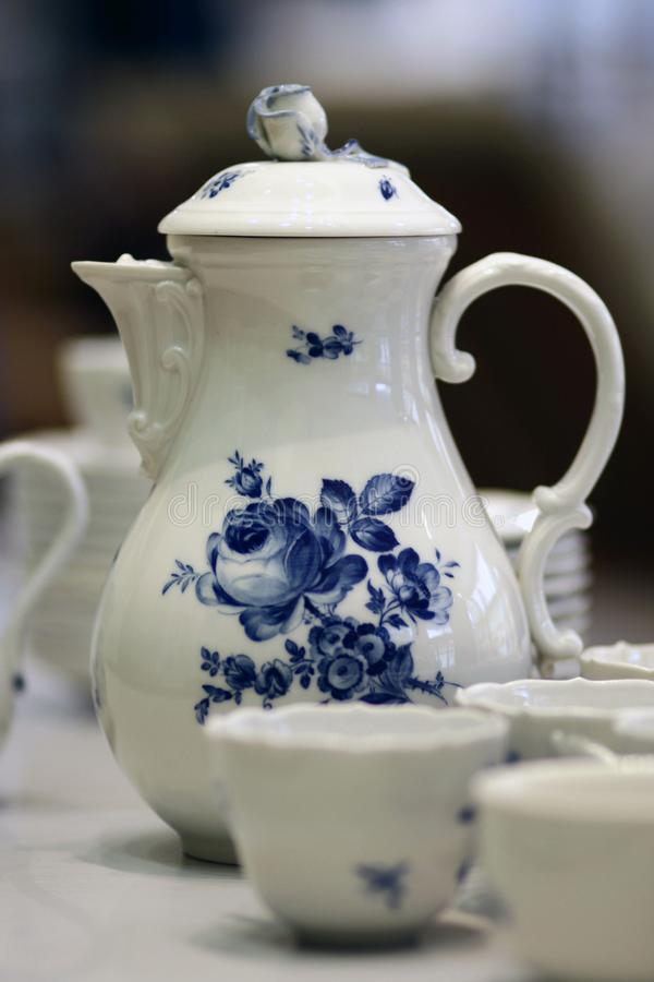 White blue porcelain coffee pot stillife Meissen. White china pot, plates, cups, bowls with blue flower decor on white background. Meissen dishes stillife stock photo