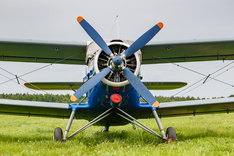White and blue soviet aircraft biplane Antonov AN-2 parked on a green grass of airfield against cloudy sky royalty free stock images