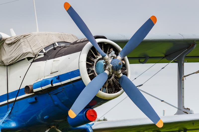 White and blue soviet aircraft biplane Antonov AN-2 at the parking on airfield closeup against cloudy sky royalty free stock photo