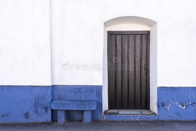 White Blue wall with bench and wooden door royalty free stock images