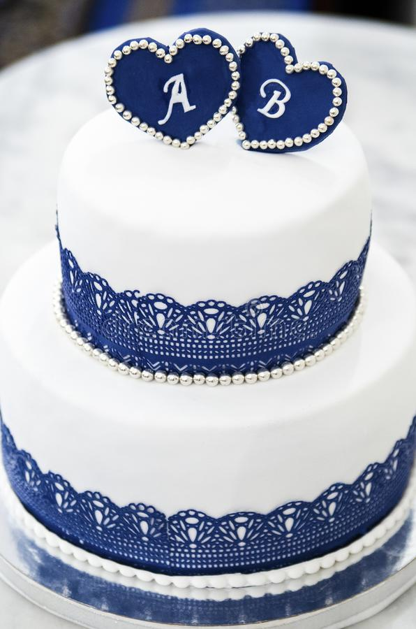 White blue wedding cake with hearts with letters. White blue wedding cake with hearts with silver beads and lace with letters A and B royalty free stock images