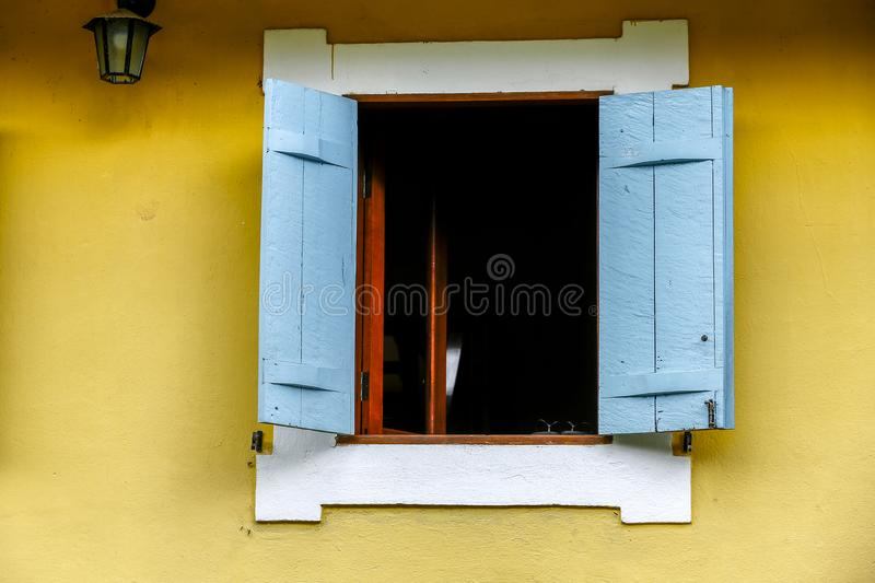 White and blue window on yellow wall royalty free stock images