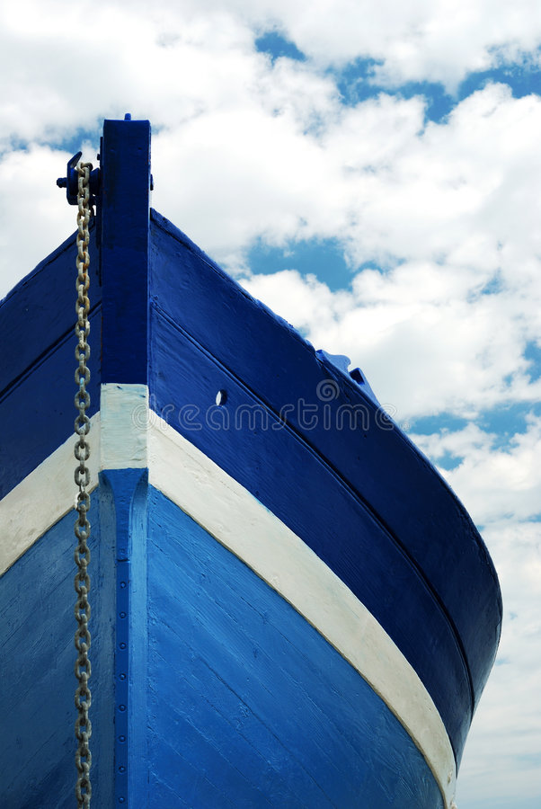 White and blue wooden boat. Front view of a wooden white and blue row fisherman boat under a cloudy sky stock photo