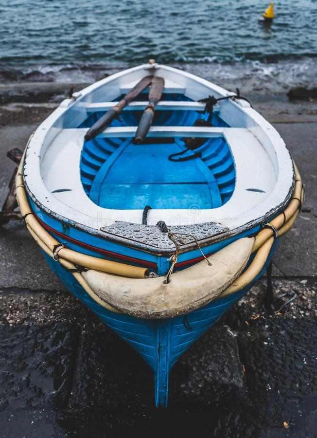White and Blue Wooden Boat on Seashore royalty free stock images