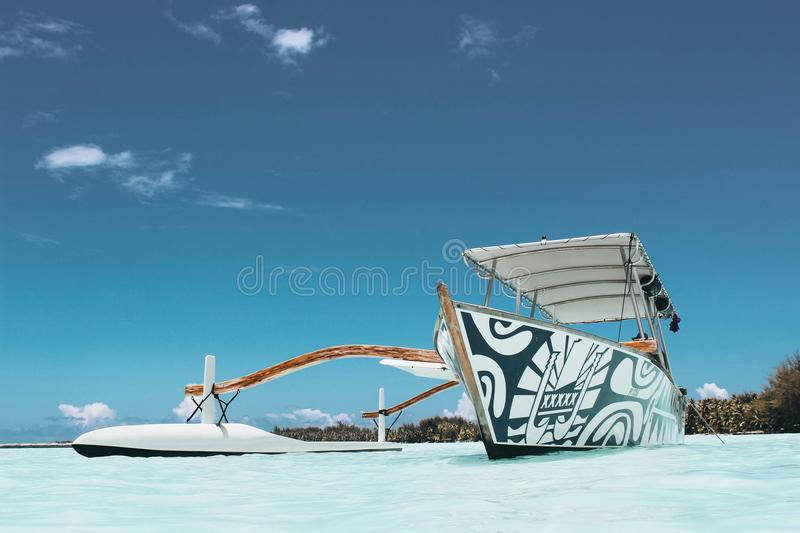 White and Blue Wooden Canoe Under Blue Sky at Daytime royalty free stock images