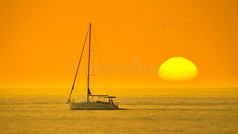 White Boat In The Middle Of The Sea During Sunset royalty free stock photos