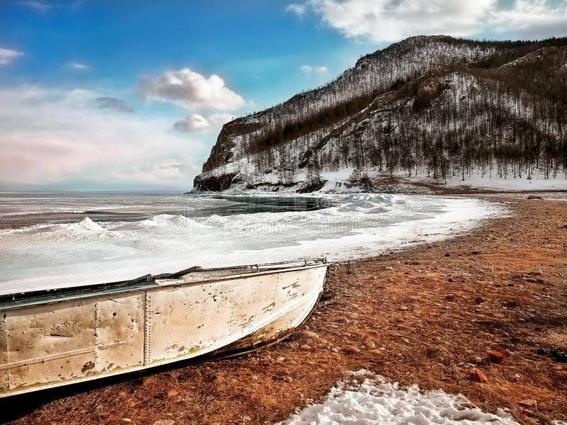 White Boat on Seashore Near Mountain Under White and Blue Sky stock photos