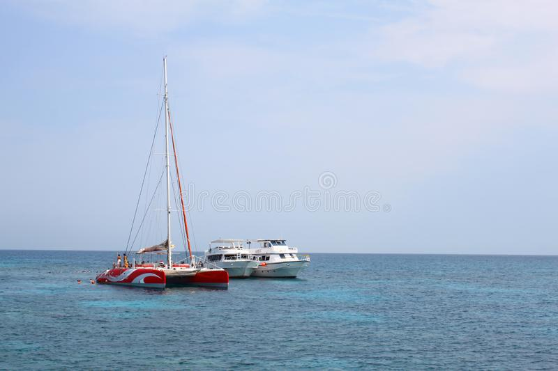 White boats, catamaran and floating people in the Red sea, Egypt stock photos