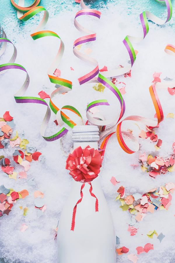 White bottle of champagne on snow with confetti and serpentine, top view. royalty free stock images