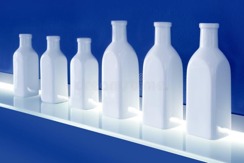 Download White Bottles Row On Blue Background Shelf Stock Photo - Image of closeup, choice: 17310552