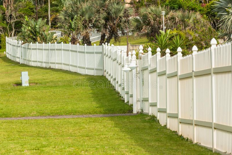 Boundary Fence Vertical Slat. White boundary vertical slat plastic pvc security fence along roade grass landscape stock photo