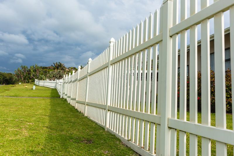 White Boundary Vertical Slat Fence. White boundary vertical slat plastic pvc security fence along roade grass landscape stock photography