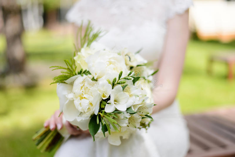 White bouquet in hands of the bride royalty free stock photo