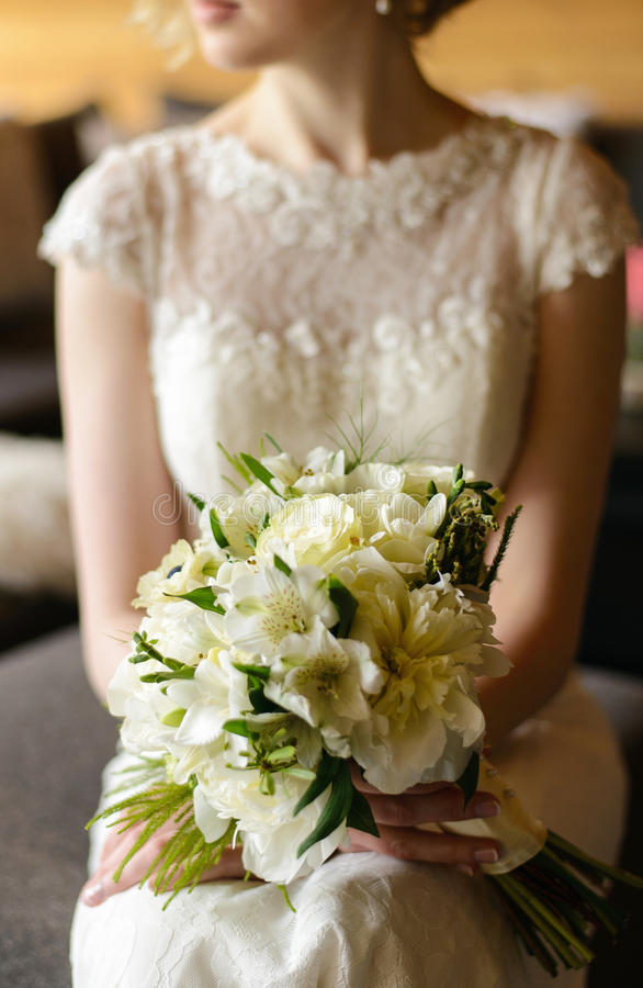 White bouquet in hands of the bride stock photography
