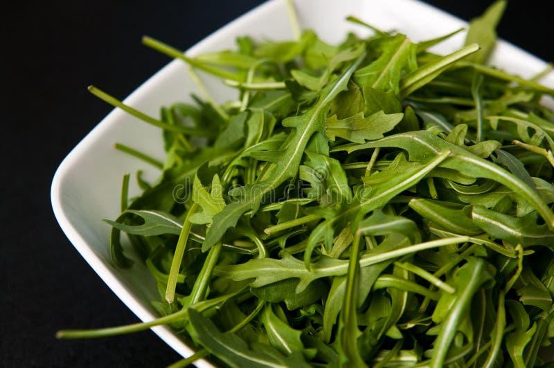 White bowl of fresh rocket salad royalty free stock photography