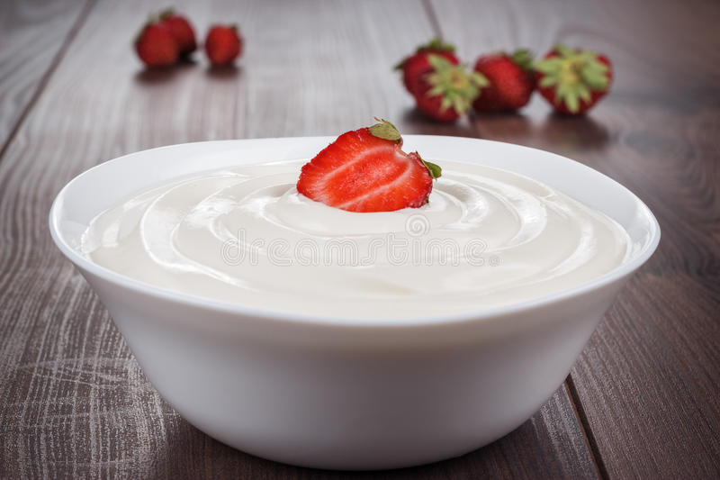 White bowl full of sour cream with strawberry stock photography