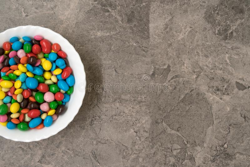 White bowl with multi colored candies royalty free stock image