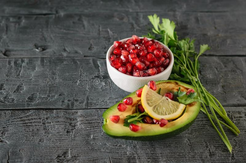 White bowl with pomegranate seeds and half avocado with pomegranate seeds stock photos