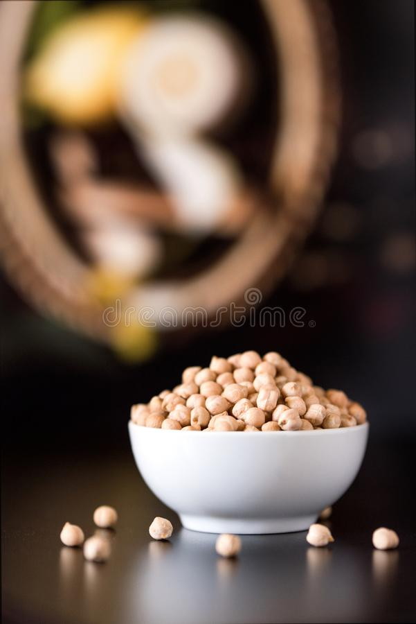 White bowl of raw chickpeas on wooden table royalty free stock photo