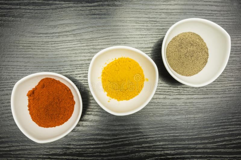 White bowls with spices - black pepper, paprika and curry. View from above. royalty free stock photo
