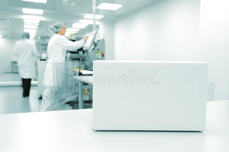 White box at automated production line. At modern factory, people working in background stock photos