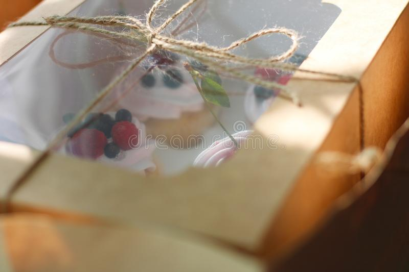 White box tied with a rope in a craft package in front of the window. Berry cupcakes under the transparent lid are ready to eat stock image