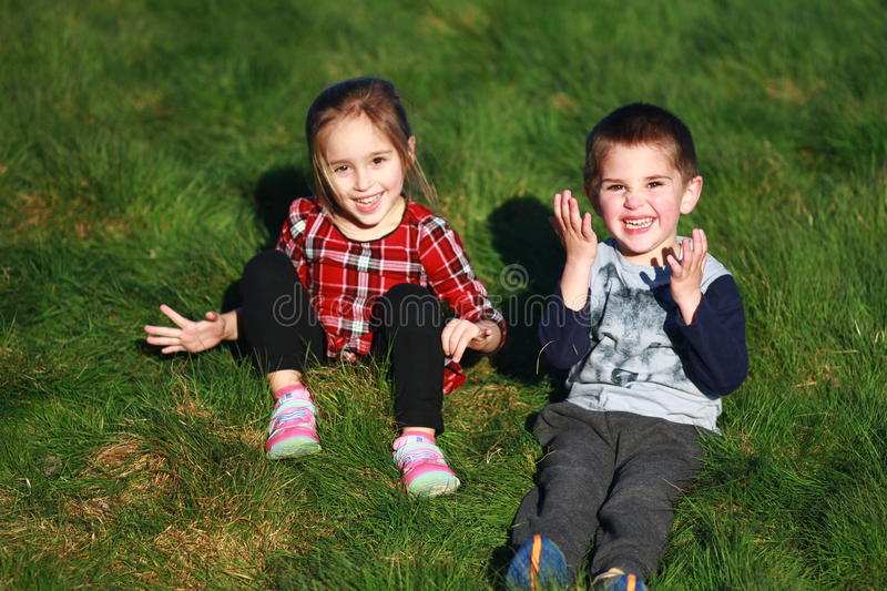 White boy - girl twins sitting on green grass royalty free stock photography