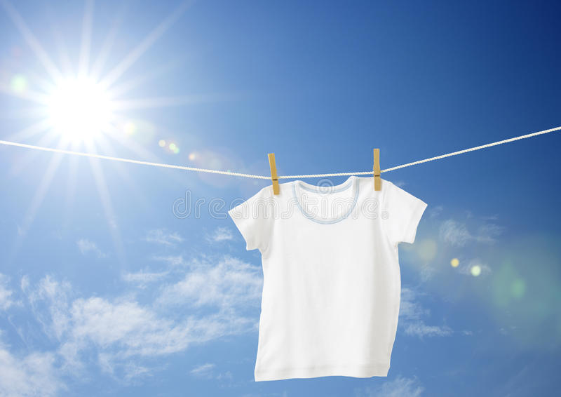 White boys T-shirt. On clothes line against blue sky