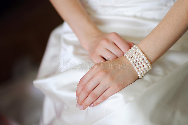 White bracelet on a hand of the bride royalty free stock image