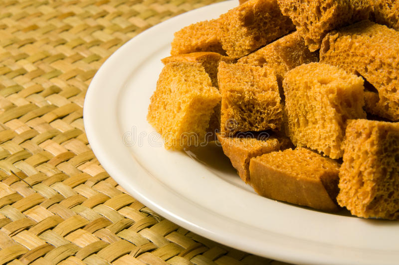 White bread croutons on white plate close-up royalty free stock photography