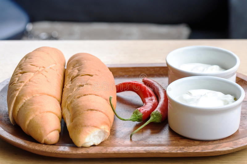 White bread and sour cream. White bread, sour cream and red pepper on a wooden plate royalty free stock images