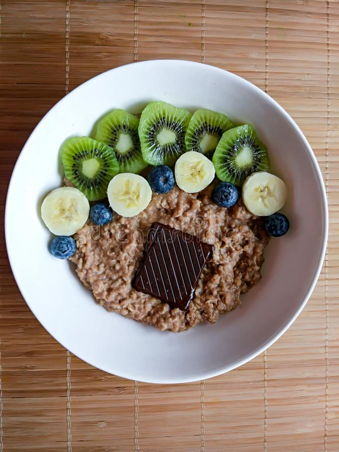 Breakfast bowl with banana, kiwi, blueberry, muesli and dark chocolate from above royalty free stock photos