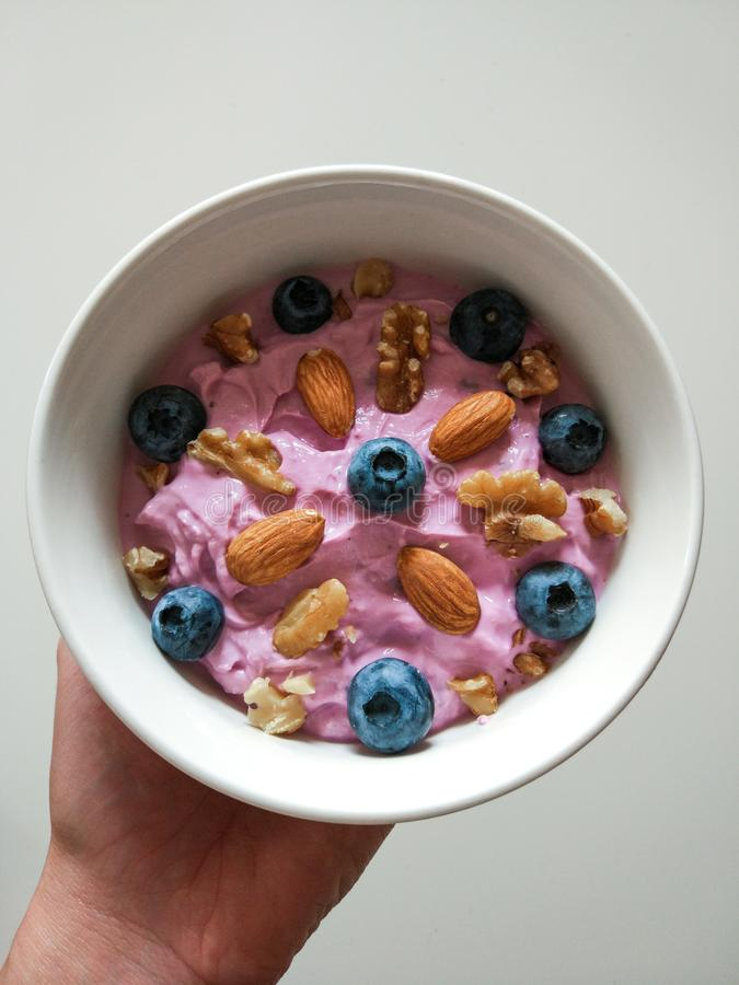 White breakfast bowl with blueberries, walnuts and almonds held by hand royalty free stock photos