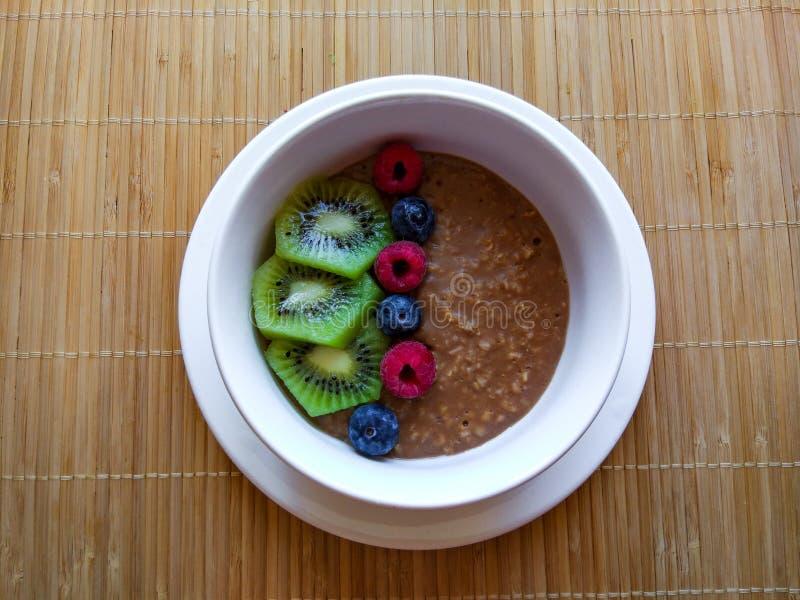 White breakfast bowl with kiwi, blueberry, raspberry and muesli on wooden background royalty free stock photo