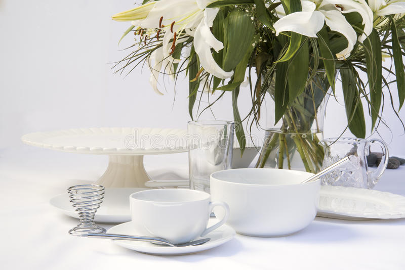 White breakfast table setting with lily flowers. Breakfast tablesetting with bright white crockery and lily flwoers stock photography
