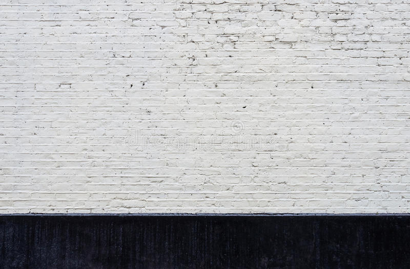 White brick wall and black skirting. Texture royalty free stock photography