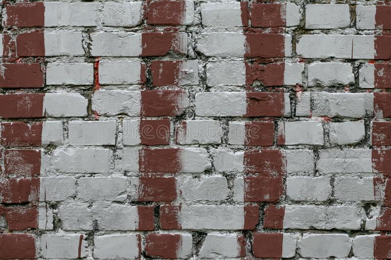 White brick wall with stripes of red paint. Old brick wall with painted red. Bricks background, pattern, texture. Grunge masonry f royalty free stock photography